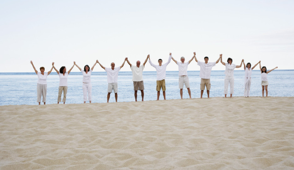 people of various ages on beach holding hands